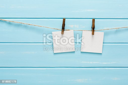 istock White blank cards on rope, blue wooden background 818682178