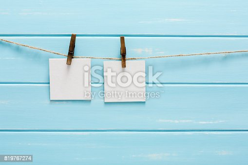 818681972istockphoto White blank cards on rope, blue wooden background 819767274