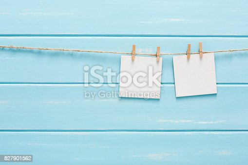 818681972istockphoto White blank cards on rope, blue wooden background 827901562