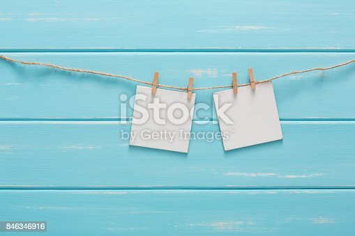 818681972istockphoto White blank cards on rope, blue wooden background 846346916