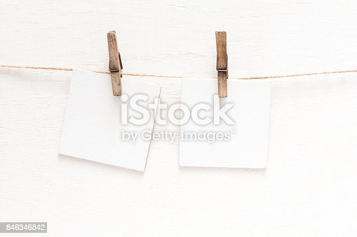 818681972istockphoto White blank cards on rope, light wall background 846346842