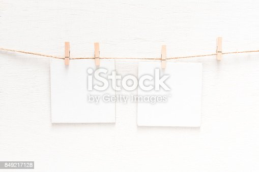 818681972istockphoto White blank cards on rope, light wall background 849217128