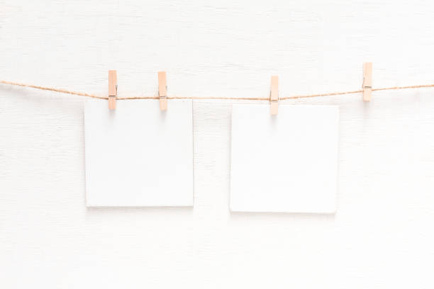 White blank cards on rope, light wall background stock photo