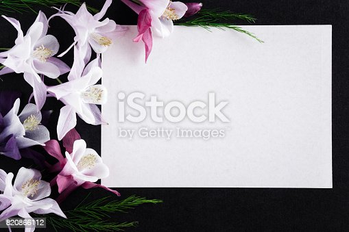 istock White blank condolence card with fresh flowers on the dark background. Empty place for a text. 820866112