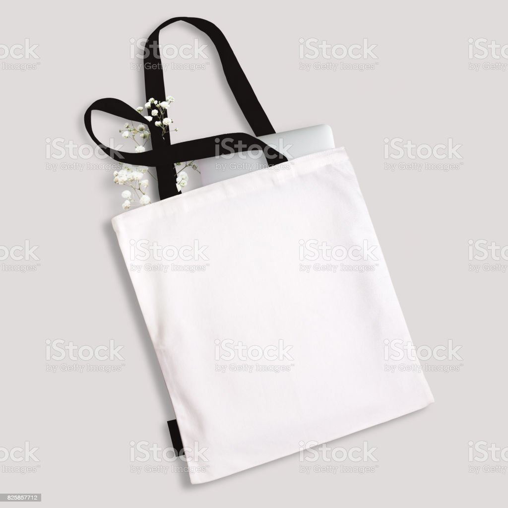 White blank cotton eco tote bag with black straps and little label, laptop and flowers inside. Design mockup stock photo