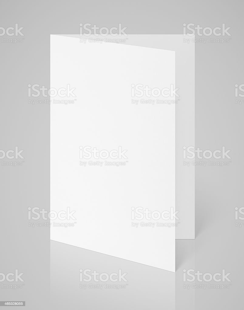 White blank folded flyer on gray stock photo
