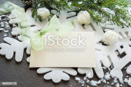 istock White blank greeting card with decorative big snowflake, snowballs and pine branches. Mock up for holiday post card and seasonal offers as advertising or other ideas. Empty place for a text. Top view. 866959728