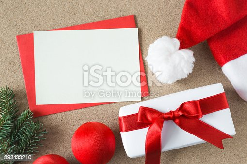 istock White blank greeting card with Santa red hat and white gift boxes with ribbons on the hot sandy tropical beach. Christmas and New Year concept. Empty place for a text. 893433210