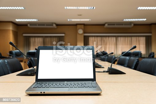 1064053478 istock photo White Blank laptop computer placed on wooden meeting table in empty meeting room. 869736620