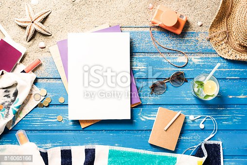White blank magazine on blue wooden beach platform with summer accessories. Directly above shot.