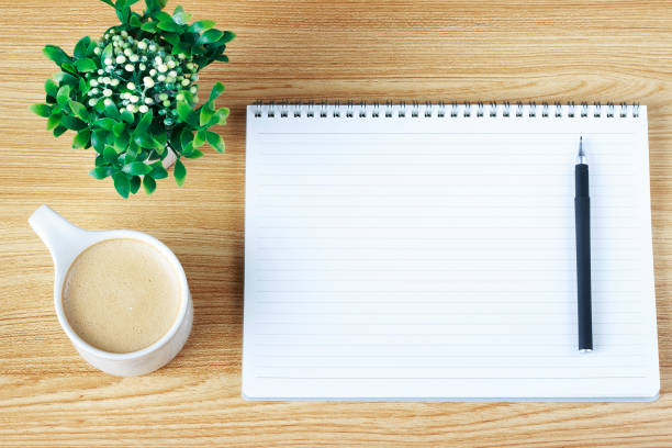White blank notebook on a wooden table, pen and coffee close-up, copy space stock photo