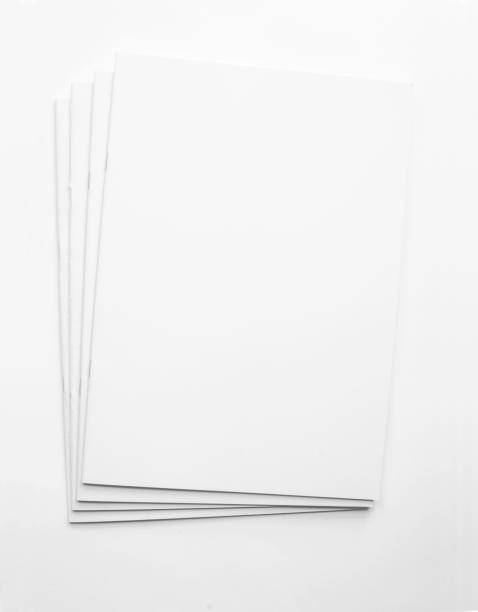 White blank paper brochure publications background Several printed magazines are laying on top of each others as a stack on white background with copy space. The templates can be used for your design ideas front page stock pictures, royalty-free photos & images