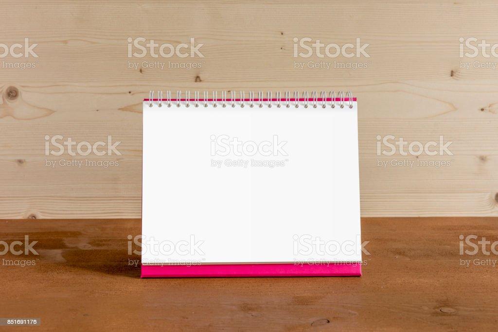 White blank paper desk spiral calendar on wood background. stock photo