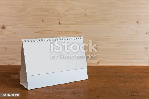 istock White blank paper desk spiral calendar on wood background. 851691220
