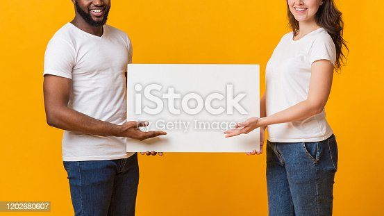 1159989540 istock photo White blank placard for your advertisement in hands of interracial spouses 1202680607