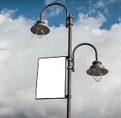 White blank rectangular billboard on a lamppost on a cloudy sky background.