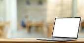istock White blank screen putting on wooden working desk or counter bar over blurred sitting room as background. 1225598342
