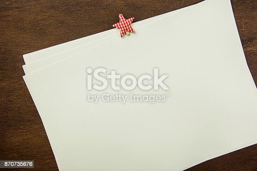 istock White Blank Sheets of Paper with Star Shape Clipper on Brown Wood Background. New Year's Resolutions Plans. Letter to Santa Clause. Christmas Party Invitation Template. Holiday Baking Recipe 870735676