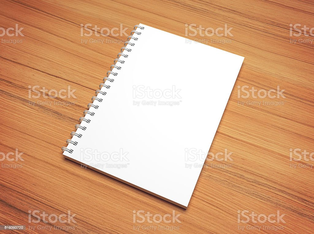 White blank spiral notepad on wooden desk texture. stock photo