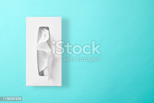 Overhead shot of opened blank tissue paper box on light blue background.