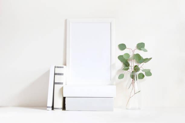 weiße leere holzrahmen mock-up mit einem grünen eukalyptus-niederlassungen in glasflasche und stapel bücher auf dem tisch liegen. plakat des produktdesigns. stockfotografie feminin gestylt. wohnkultur - vase glas stock-fotos und bilder