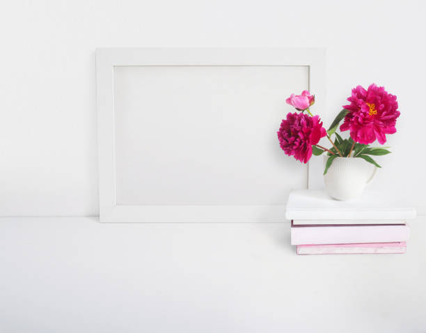 white blank wooden frame mockup with a peony flowers bouquet in a porcelain cup and pile of books lying on the table. poster product design. styled stock feminine photography. home decor. - chinese peony zdjęcia i obrazy z banku zdjęć