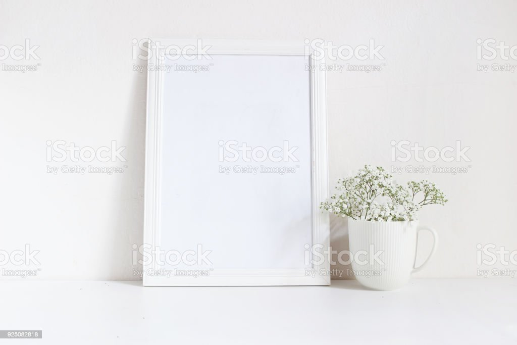 White blank wooden frame mockup with baby breath, Gypsophila flowers in porcelain mug on the table. Poster product design. Styled stock feminine photography. Home decor stock photo