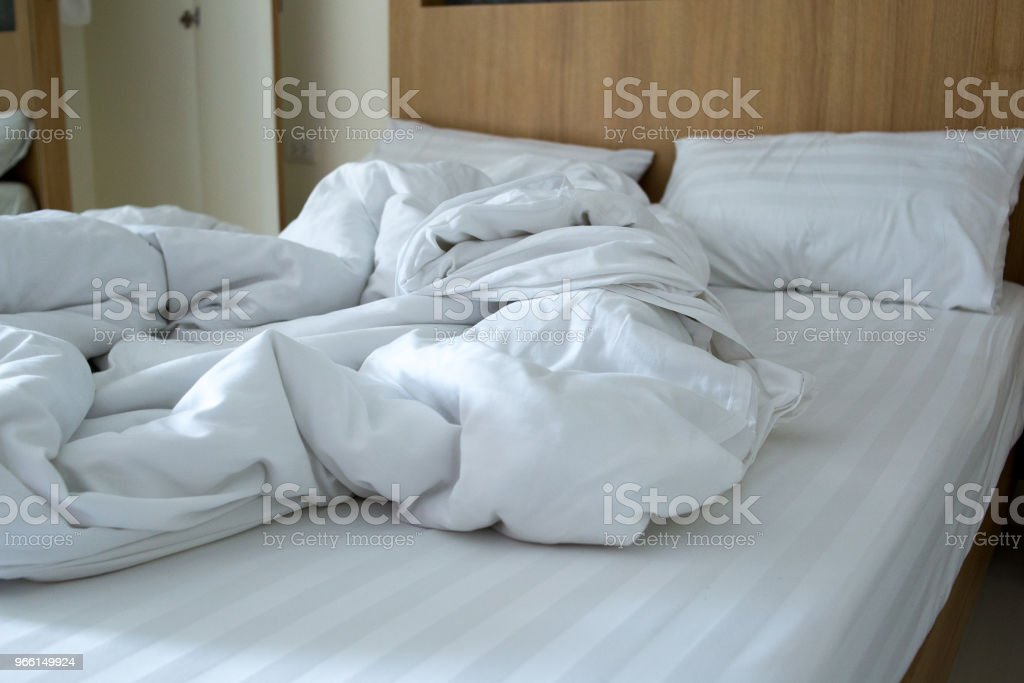 white blanket dishevelled on the bed - Foto stock royalty-free di Albergo