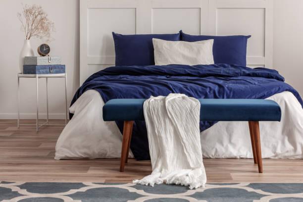 weiße decke auf samtbank im essen des doppelbettes - marineblau schlafzimmer stock-fotos und bilder