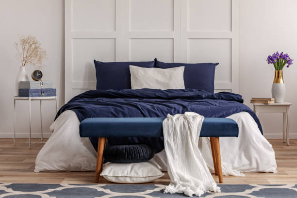 White blanket on velvet bench in the food of double bed – zdjęcie