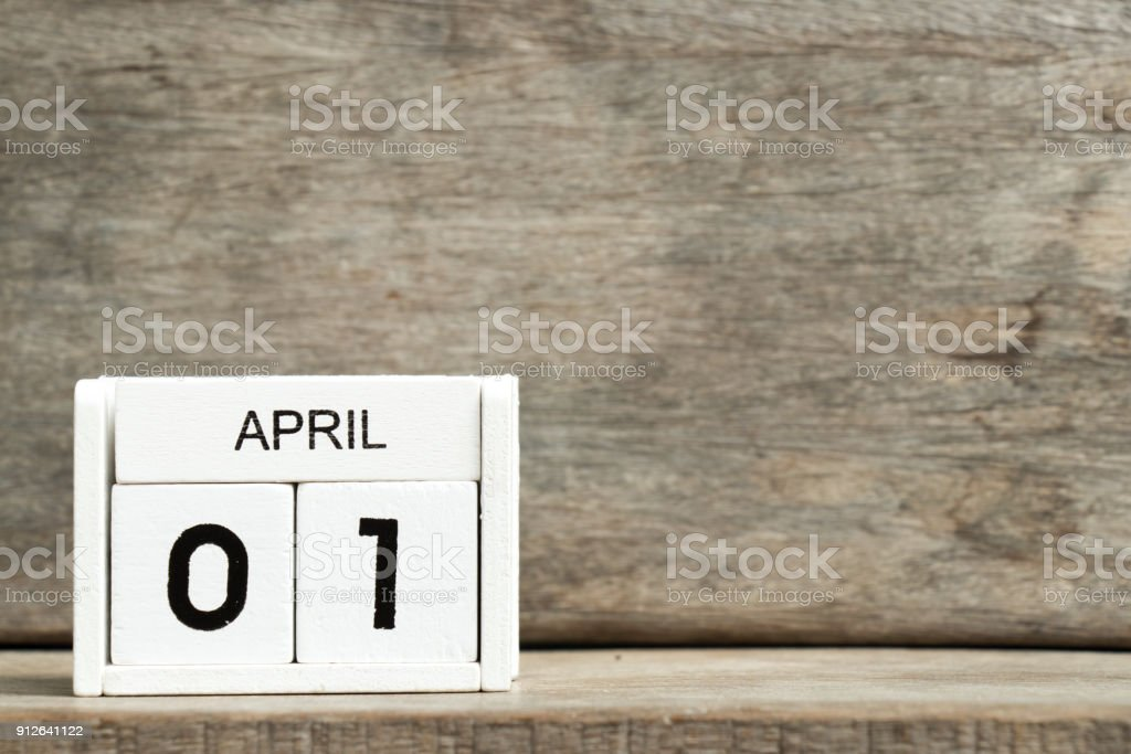 White block calendar present date 1 and month April on wood background stock photo