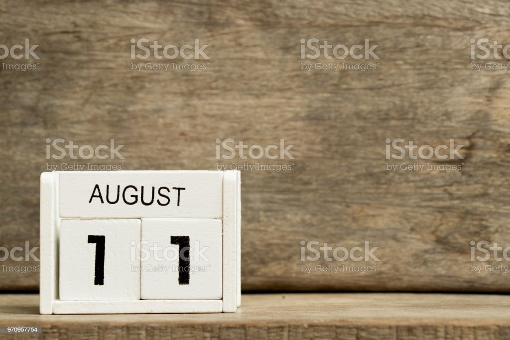 White block calendar present date 11 and month August on wood background stock photo