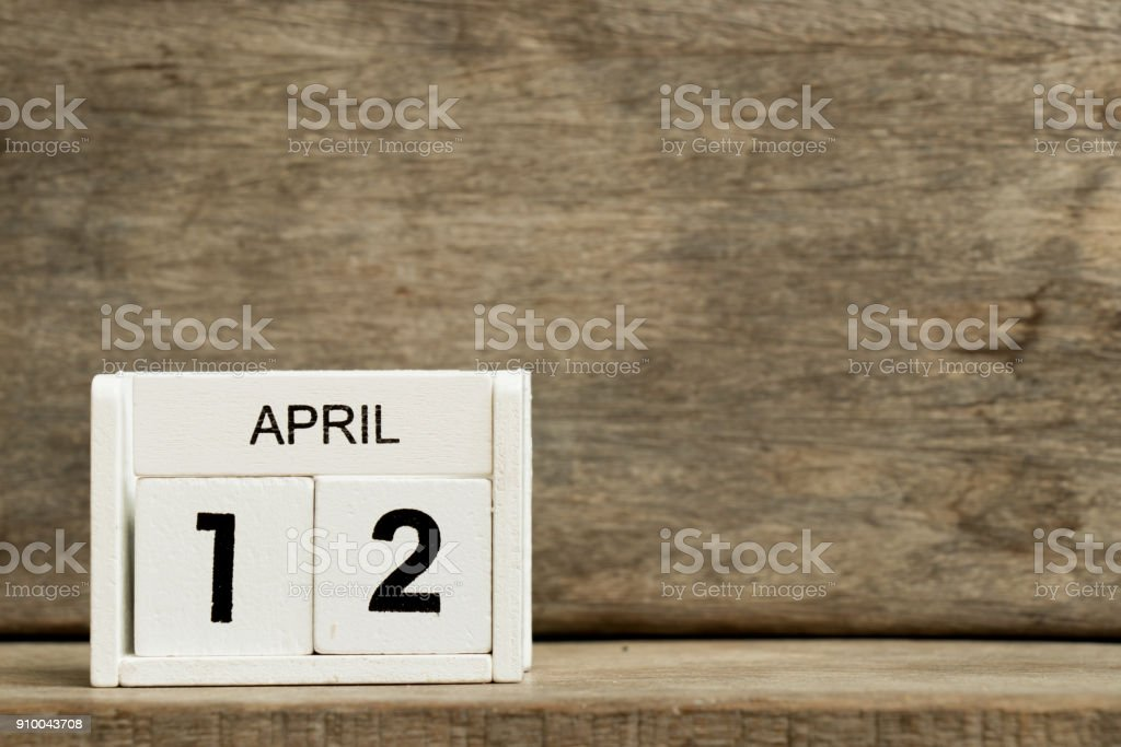 White block calendar present date 12 and month April on wood background stock photo