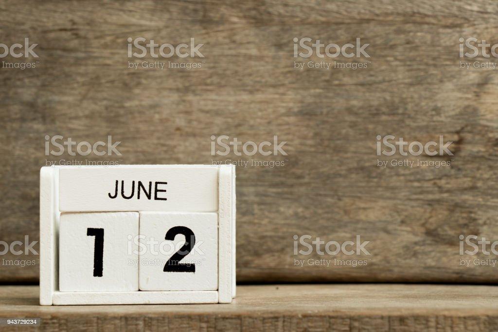 Calendário bloco branco presente data 12 e o mês de junho em fundo madeira - foto de acervo