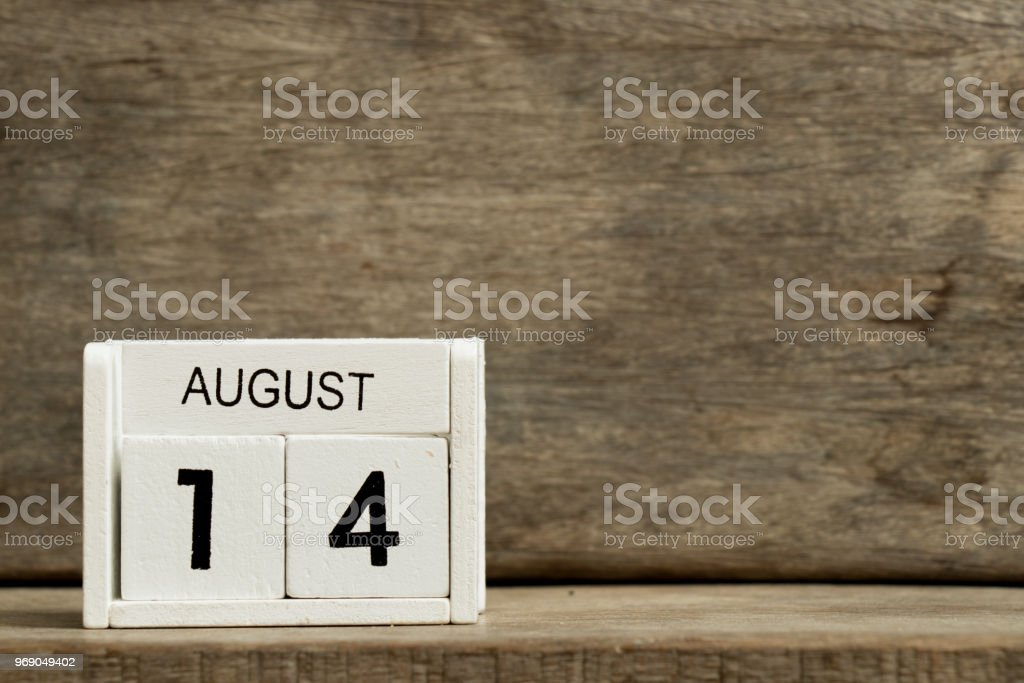 White block calendar present date 14 and month August on wood background stock photo