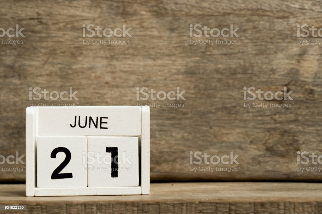 White block calendar present date 21 and month June on wood background stock photo