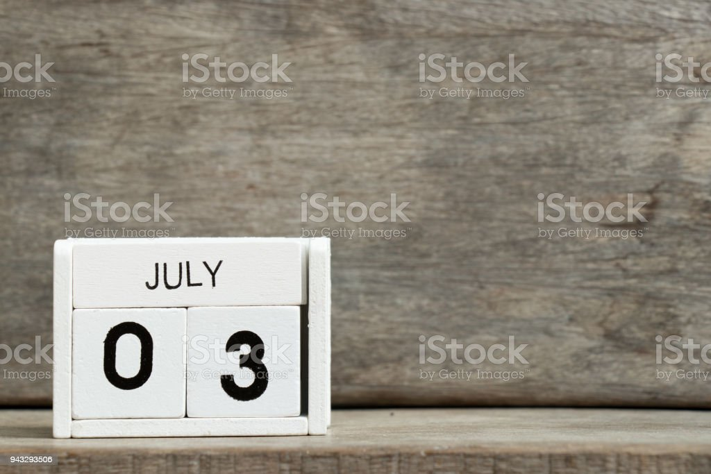 White block calendar present date 3 and month July on wood background stock photo