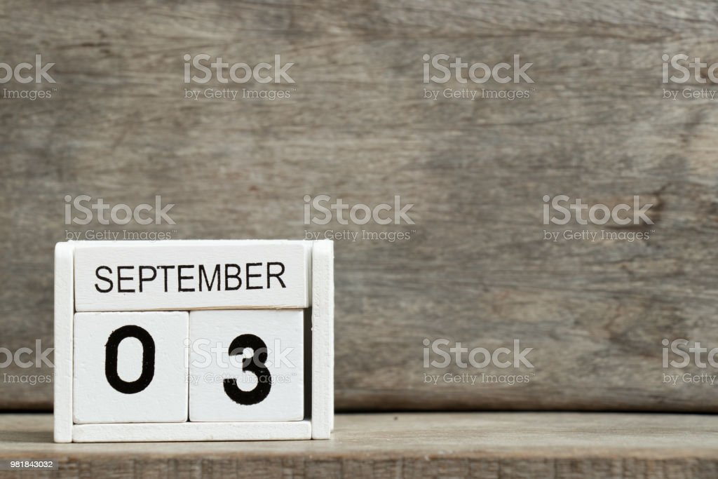 White block calendar present date 3 and month September on wood background stock photo