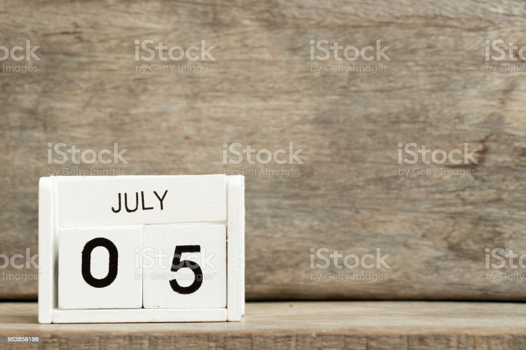 White block calendar present date 5 and month July on wood background stock photo