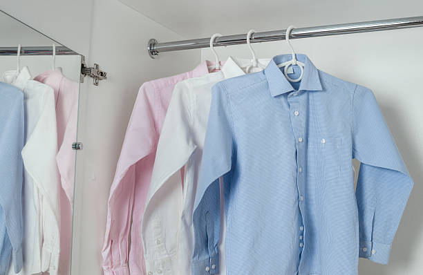 white, blue and pink clean ironed men's shirts stock photo