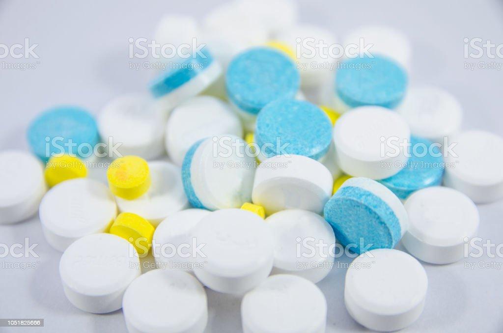 istock white, blue and yellow pill on white blackground 1051825666