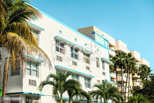 White, blue, teal, turquoise, yellow buildings in Art Deco district in South Beach of Miami, Florida during sunny day with palm trees, balconies, windows