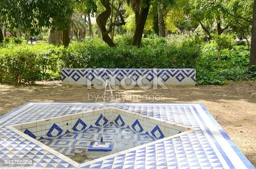 White blue tiles fountain and bench in Park of  Seville, Andalusia, Spain.