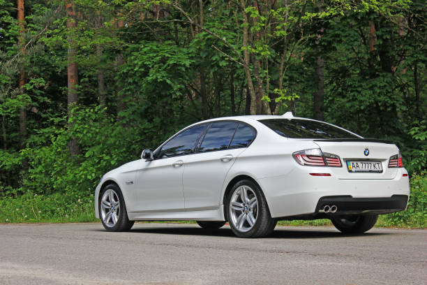 White BMW 520 TDI (F10) M Sport in the forest stock photo