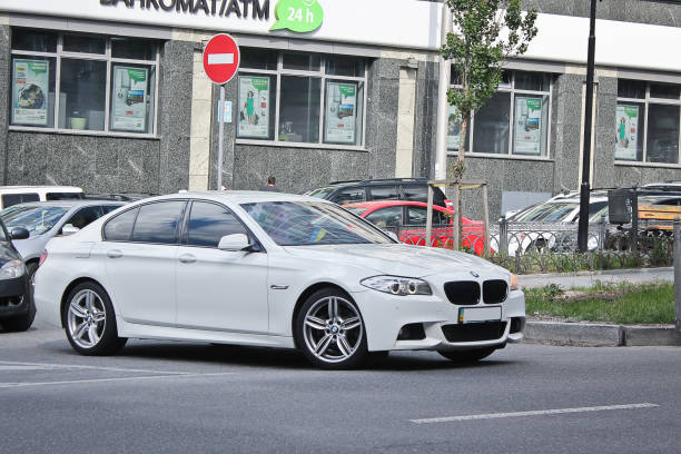 White BMW (F10) in motion. Car in the city stock photo