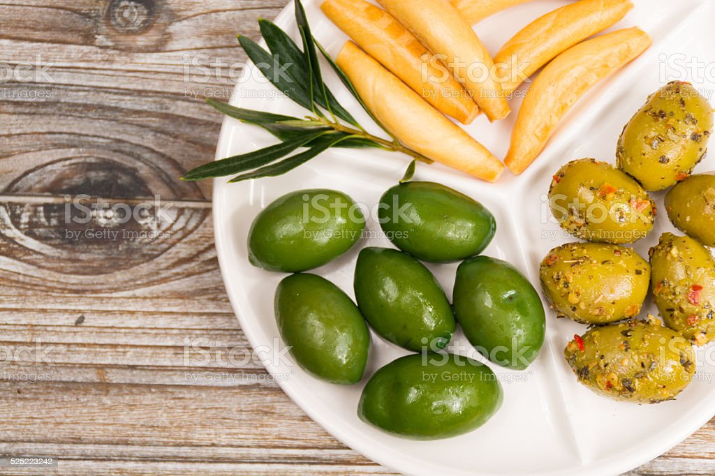 White board with giant  green olives and bread stock photo