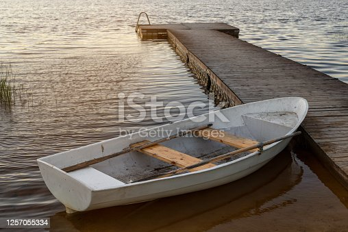 Aerial view of small white boat floating on the lake near pier