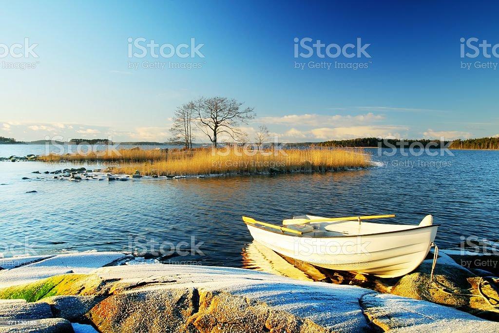 White boat near rocks over blue sky royalty-free stock photo