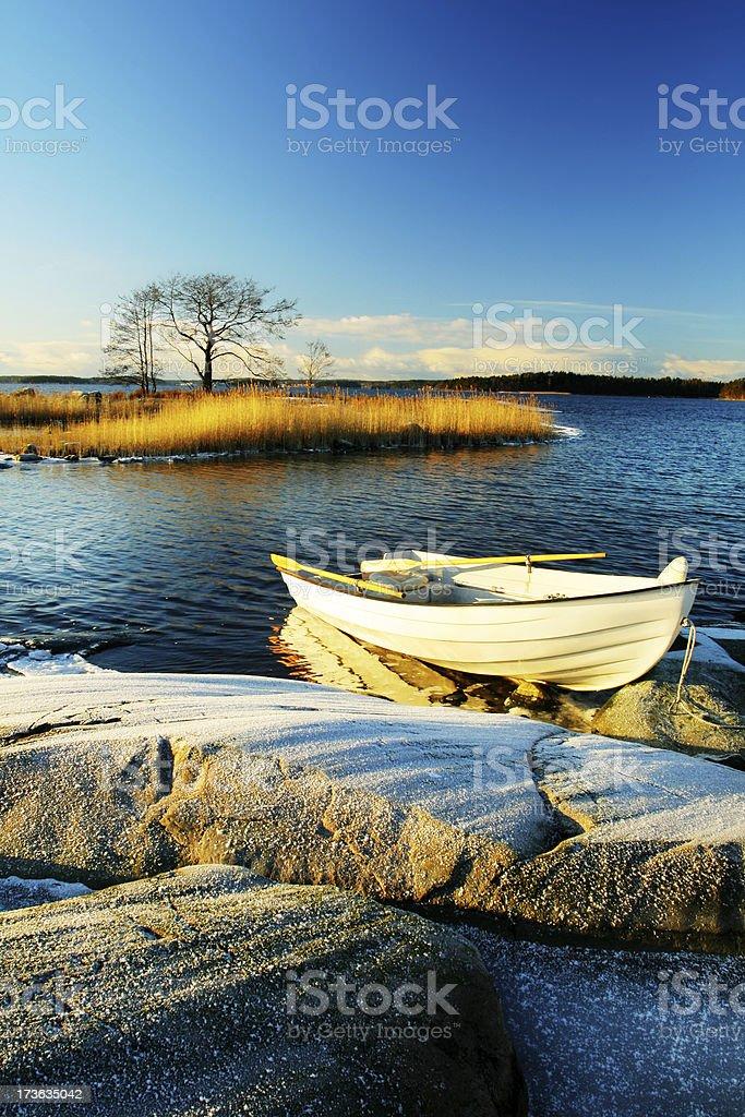 White boat near rocky lakeside over blue sky royalty-free stock photo