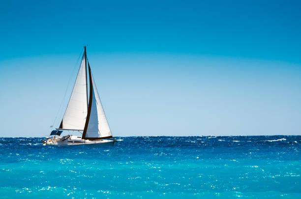 Barco branco navegando no mar azul - foto de acervo
